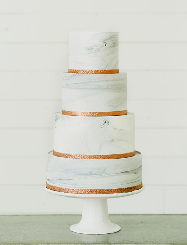 a four-tier white marble wedding cake decorated with copper ribbons is a stylish solution for a modern wedding