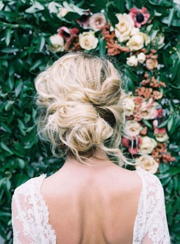a messy low updo with a bump on top and some locks down is a chic idea for a modern and casual bride