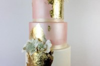 a statement wedding cake in ivory and pink, with lots fo gold leaf and edible flowers to accent it