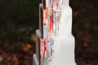 a catchy square wedding cake decorated with colorful touches and gold leaf looks bold and unusual
