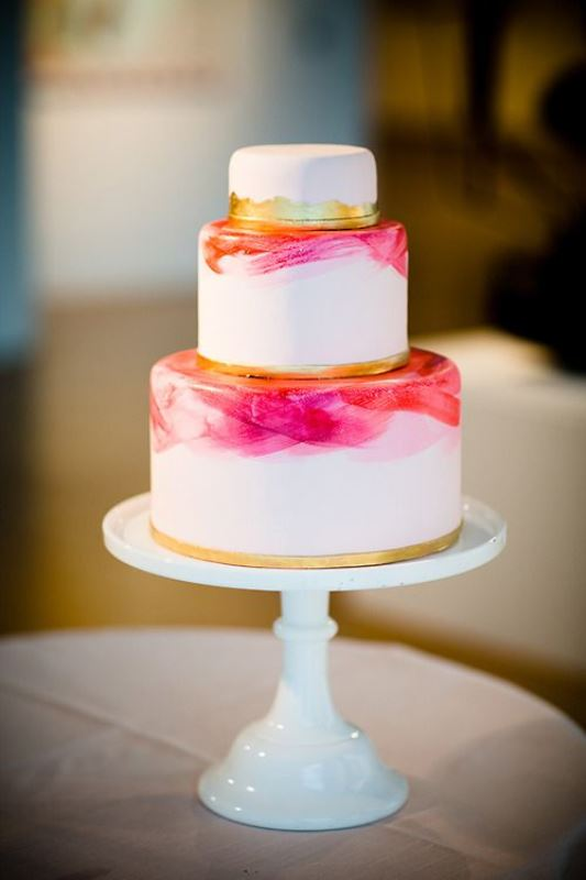 a white wedding cake with bright pink watercolors and gold leaf touches to make it more sparkly and glam