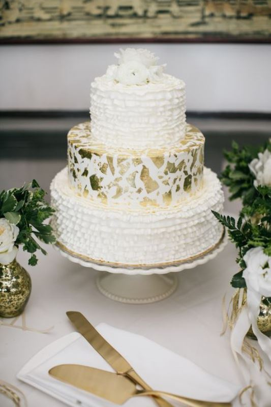 a catchy wedding cake with two ruffle tiers and a single white tier with gold leaf plus some fresh white blooms on top
