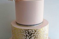 a pink wedding cake with a floral gold leaf tier and a large pink sugar flower on top looks very romantic