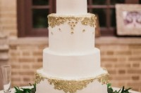 a stylish white wedding cake decorated with gold leaf, with a calligraphy topper and a greenery stand