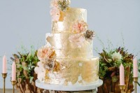 a bold gold leaf wedding cake decorated with sugar flowers looks very whimsy and very glam-like