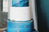 a creative wedding cake with two blue watercolor tiers, a white tier with calligraphy, gold leaf looks very eye-catching