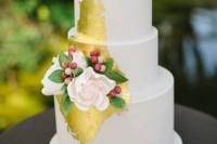 a white wedding cake with lots of gold leaf, with fresh blooms, leaves and berries looks glam and pretty