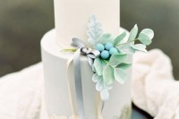 a delicate wedding cake in white and powder blue, with with sugar leaves, berries and some ribbons is a perfect fit for spring