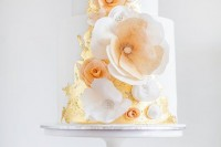 a white wedding cake with gold leaf and lots of sugar blooms of various sizes looks very catchy and very cool