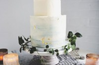 a textural buttercream wedding cake in white and blue watercolors with gold leaf looks very delicate and very chic