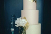 a pastel green and pink wedding cake decorated with gold leaf, with large sugar blooms is a chic idea for spring