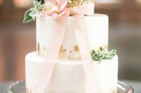 a white wedding cake with gold leaf touches and a gold sequin tier on top, with greenery, a pink bow and a pink bloom