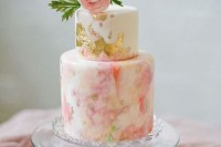 a bright pink watercolor wedding cake decorated with gold leaf and accented with a single pink bloom on top