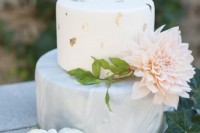 a modern wedding cake of a grey marble tier, a white one with gold leaf and a large blush bloom