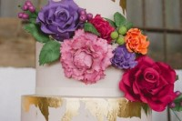 a white wedding cake with gold leaf, with edible and real colorful blooms and sugar leaves and berries