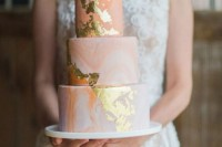 a trendy peachy marble wedding cake with gold leaf is a chic and cute idea for a modern wedding