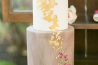 a pretty wedding cake with a taupe marble tier, a white one, painted flowers, gold leaf and a large sugar bloom on top