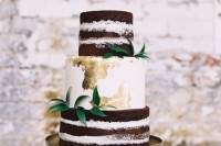 a naked and buttercream wedding cake with gold leaf and greenery for decor