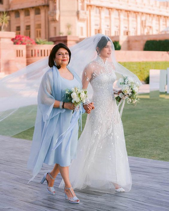 Priyanka Chopra's mother wearing a powder blue midi dress and a coverup plus matching shoes