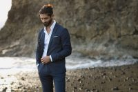 a beach groom outfit with a graphite grey suit, a white shirt, barefoot and a beard and a wavy man bun is lovely