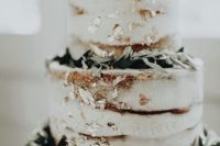 a beautiful naked wedding cake decorated with gold leaf and greenery looks simple and very stylish
