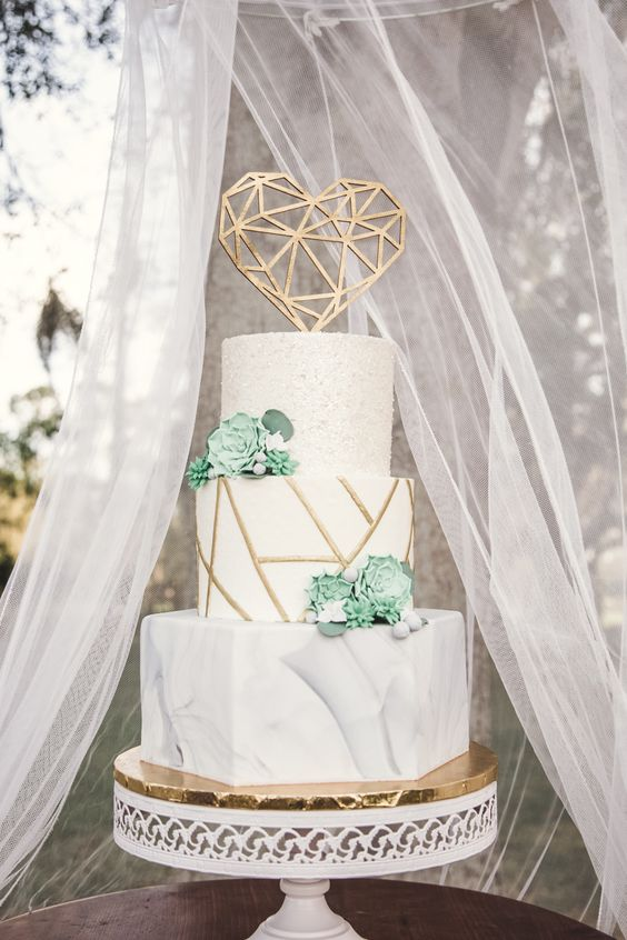 a beautiful wedding cake with a white marble, geometric and textural tier, with succulents and a gold geometric heart
