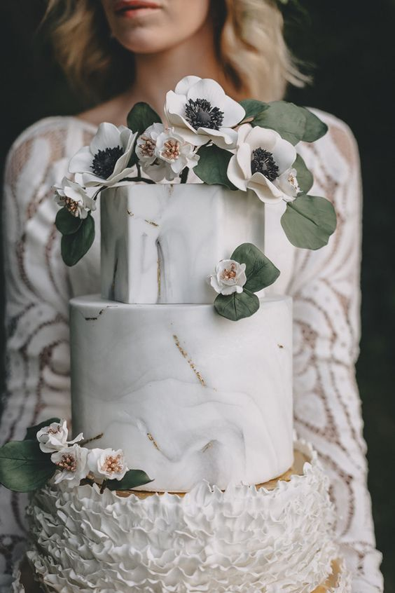 a beautiful wedding cake with marble and ruffle tiers and gold leaf and blooms and leaves on top for a refined wedding