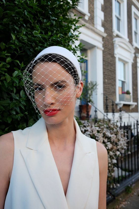 a birdcage veil with a white headband is a modern and bold idea for a refined bride