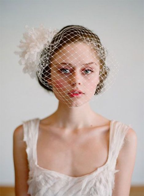 a birdcage veil with an oversized fabric bloom on one side is a stylish idea to rock and a touch of vintage glam