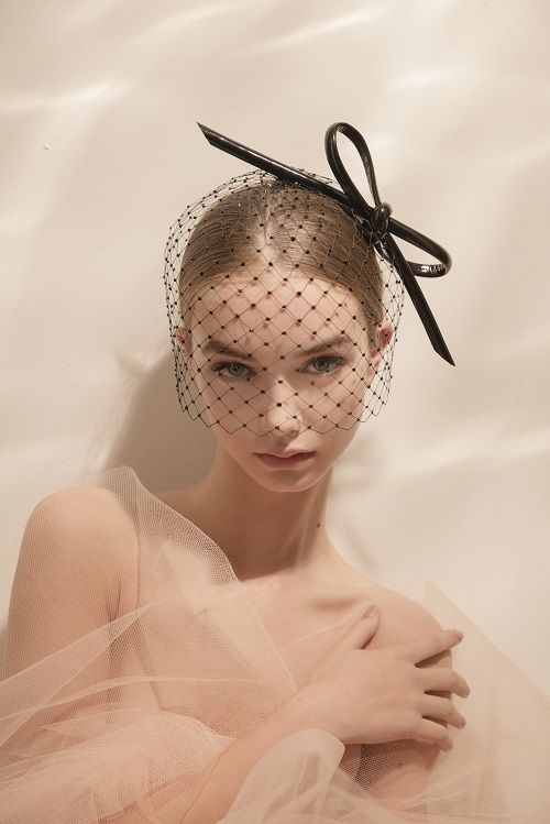 a black birdcage veil with crystals and an oversized black leather bow for a modern and girlish look