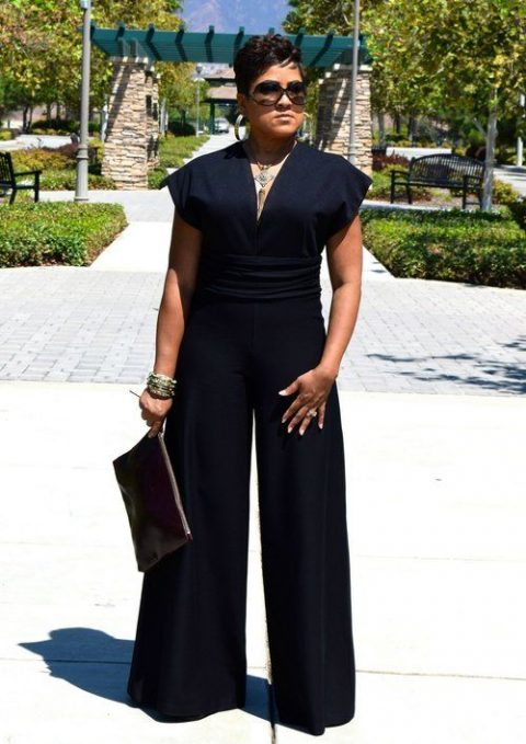 a black jumpsuit with wideleg pants, cape sleeves, a high waist and a statement necklace