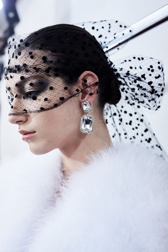 a black polka dot veil with a large bow on the back is a statement idea for a modern bride