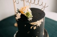 a black textural wedding cake with gold leaf, neutral blooms, berries and thistles looks very chic