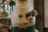 a black, white wedding cake with gold leaf, with bold and pastel blooms and greenery for a bold wedding in fall or winter