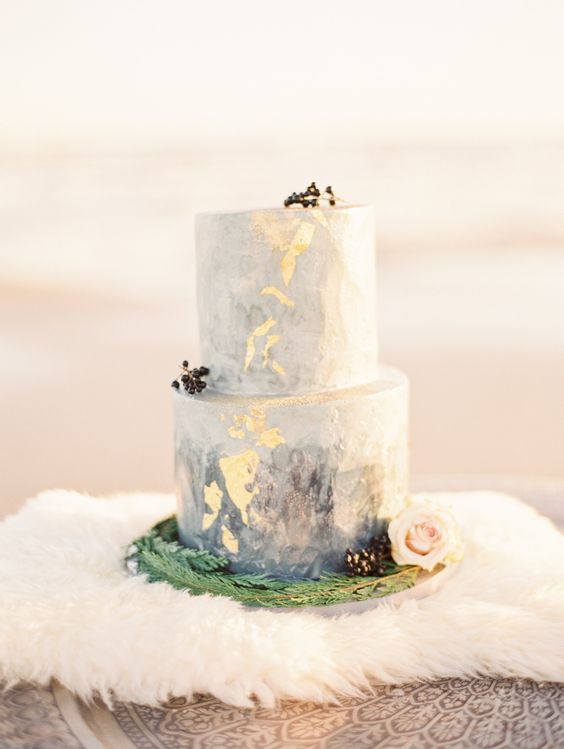 a blue watercolor wedding cake with gold leaf, privet berries and blush blooms looks delicate and chic
