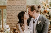 a boho groom look with a grey suit, a white shirt, a bolo tie and a messy man bun for a relaxed touch