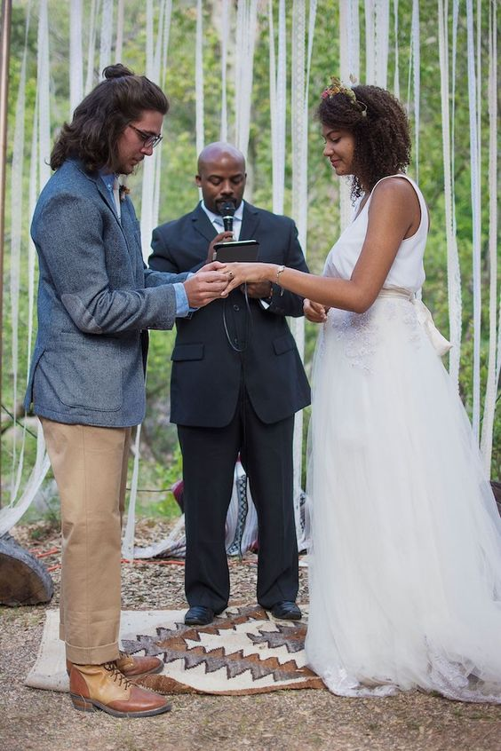 a boho groom outfit with a blue shirt, a tan tie and pants, a grey blazer, two tone boots and a man bun plus hair down