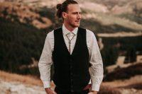 a boho groom outfit with a white shirt, a black waistcoat, black pants, a bolo tie and a man bun is wow