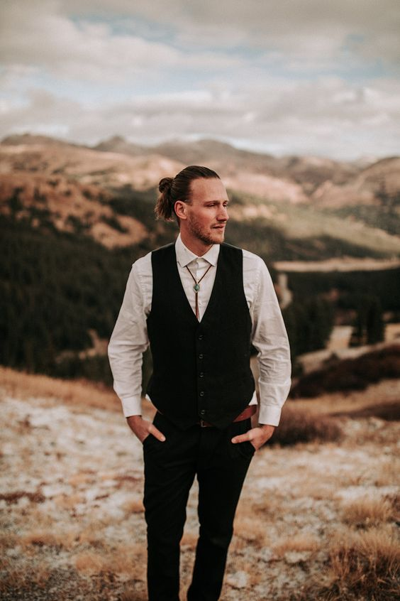 a boho groom outfit with a white shirt, a black waistcoat, black pants, a bolo tie and a man bun is wow
