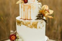 a boho white wedding cake with caramel drip, gold leaf, bold fall blooms and feathers plus a calligraphy topper