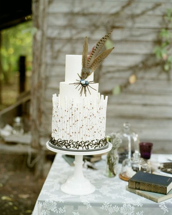 a boho white wedding cake with plain tiers, cookies, some candies and feathers for a boho wedding