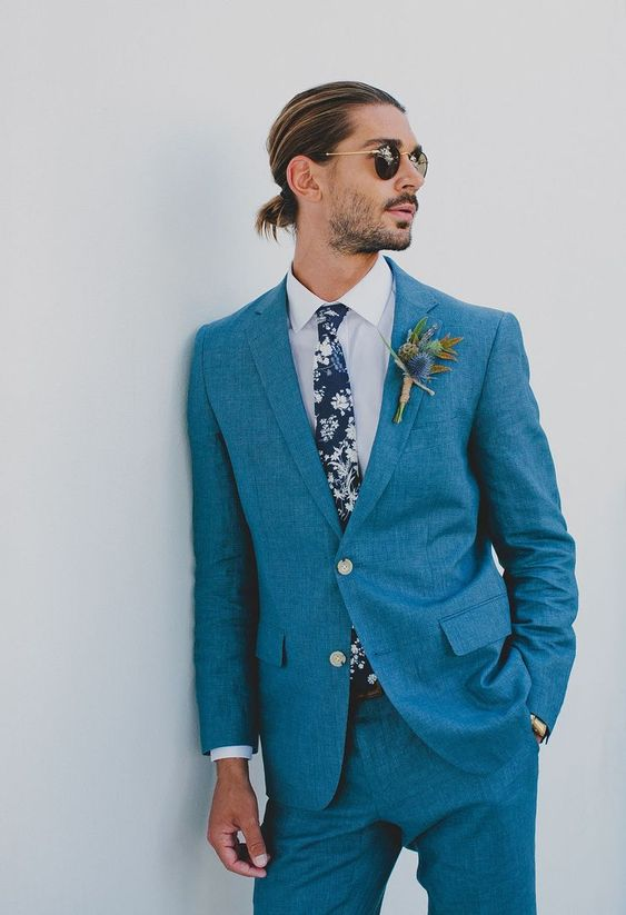 a bold blue suit, a dark floral tie, a white shirt and a man bun for a relaxed and very stylish groom's look