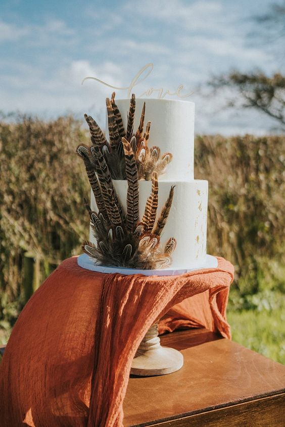 a bold boho wedding cake in white, with lots of feathers is a chic and cool dessert for a wild celebration