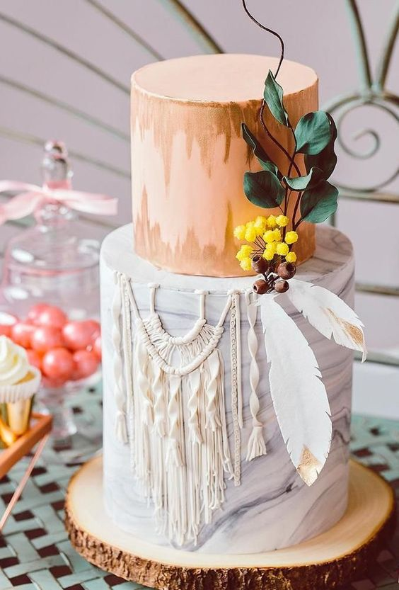 a bold boho wedding cake with a coral and grey marble tier, feathers, sugar macrame and berries and leaves