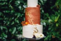 a bold fall wedding cake with textural white and rust tiers, gold leaf, bold and white blooms and some berries