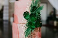 a bold pink watercolor wedding cake with gold leaf and tropical leaves is amazing for a tropical wedding