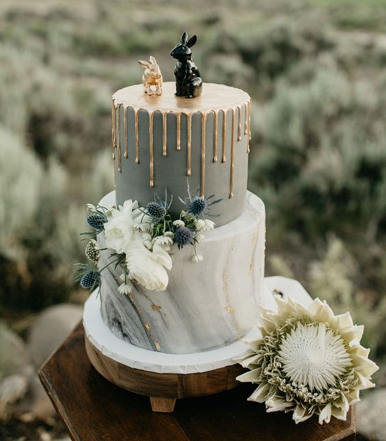 a bold wedding cake with a grey and grey marble tier, gold drip, white blooms, thistles and fun bunny cake toppers