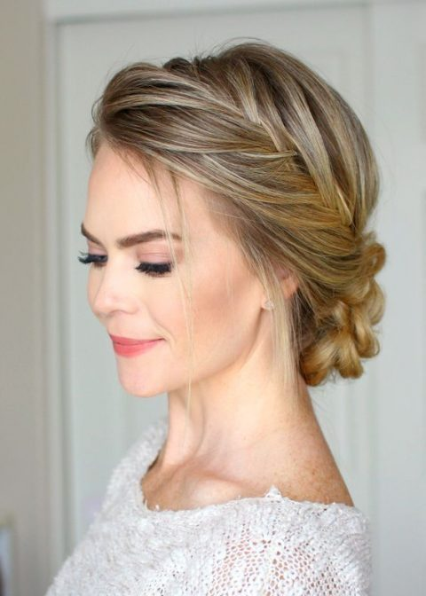 a braided side halo with a braided low bun and some locks down for a rustic or boho bride