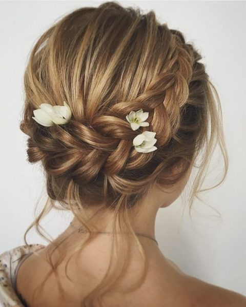 a braided updo with locks down, a dimensional bump and fresh blooms tucked into the braid