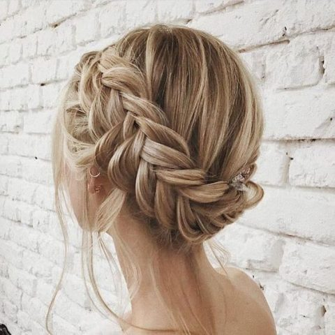 a braided updo with some locks down and some fresh blooms is a chic idea for a boho bride